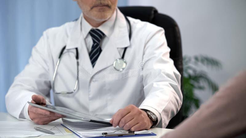 Cuide la comprobación de datos de los pacientes sobre la tableta, guardando informes médicos, consulta fotografía de archivo libre de regalías