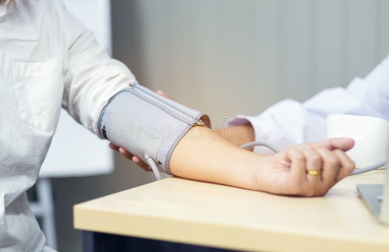 Cuide la comprobación de la presión arterial del foco paciente, selectivo, foto de archivo libre de regalías