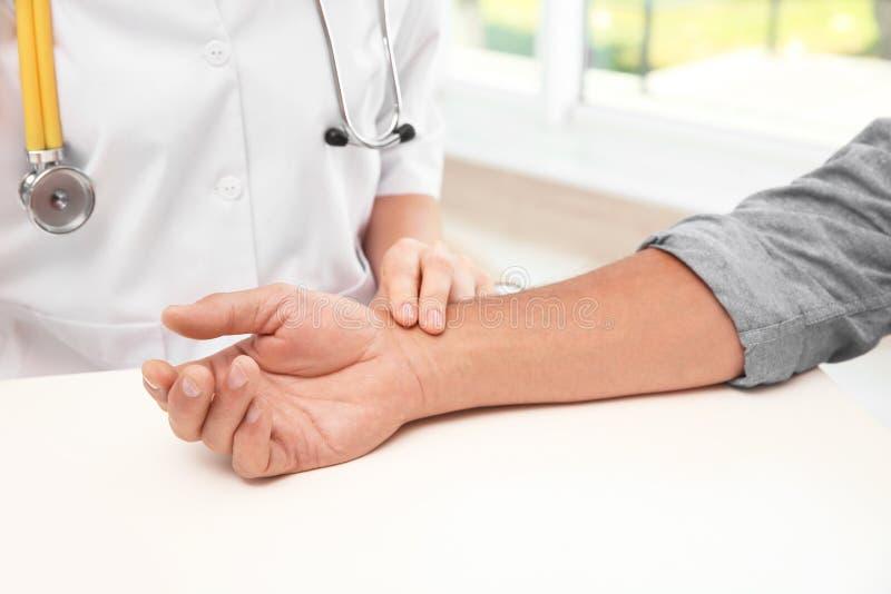 Cuide la comprobación de pulso del ` s del hombre mayor en hospital foto de archivo