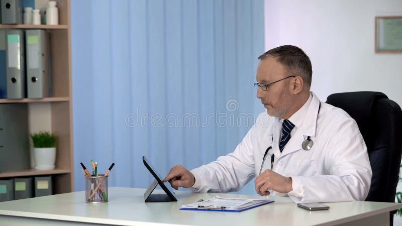 Cuide la custodia de informes médicos de los pacientes en la tableta, base de datos moderna del hospital fotos de archivo libres de regalías