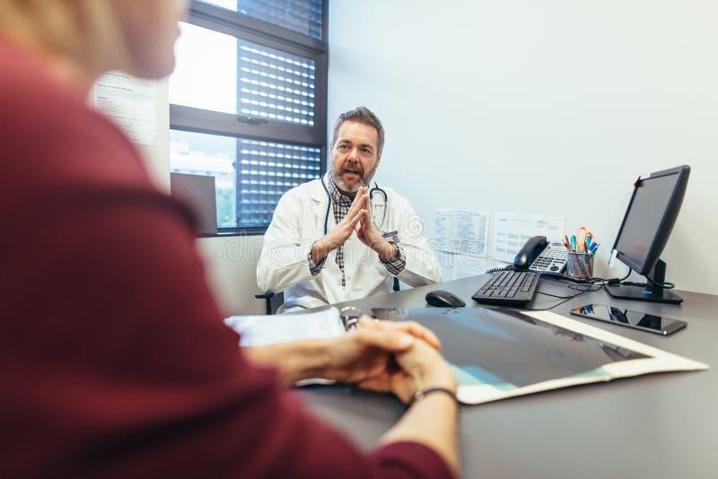Cuide la discusión con el paciente femenino en su clínica fotografía de archivo