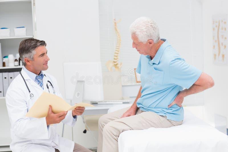 Cuide la discusión de informes con el paciente que sufre de dolor de espalda fotografía de archivo
