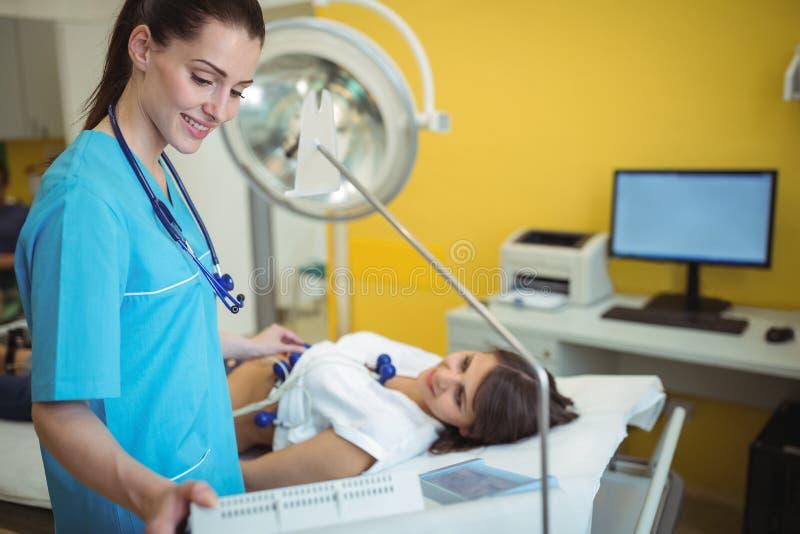 Cuide la ejecución de una prueba del electrocardiograma en el paciente fotos de archivo