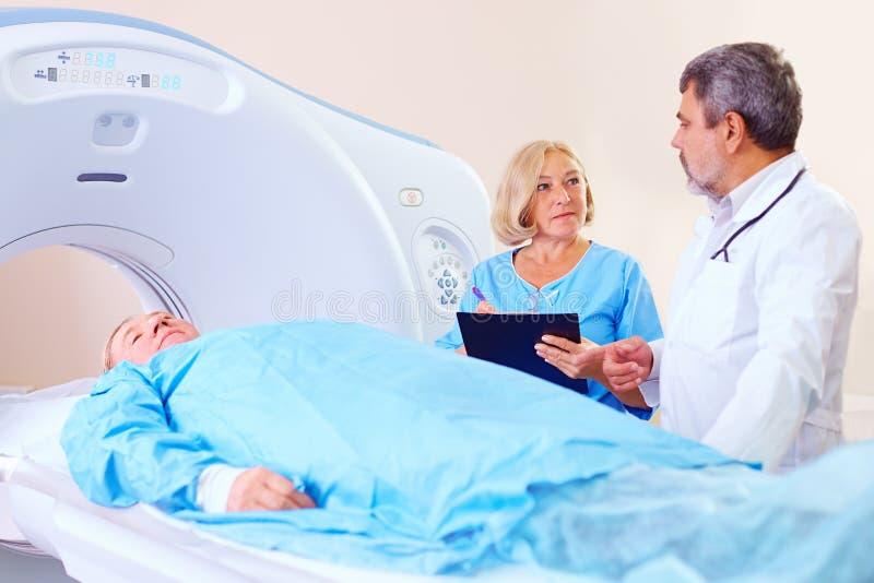 Cuide la instrucción del personal médico sobre procedimiento del escáner del CT imagen de archivo