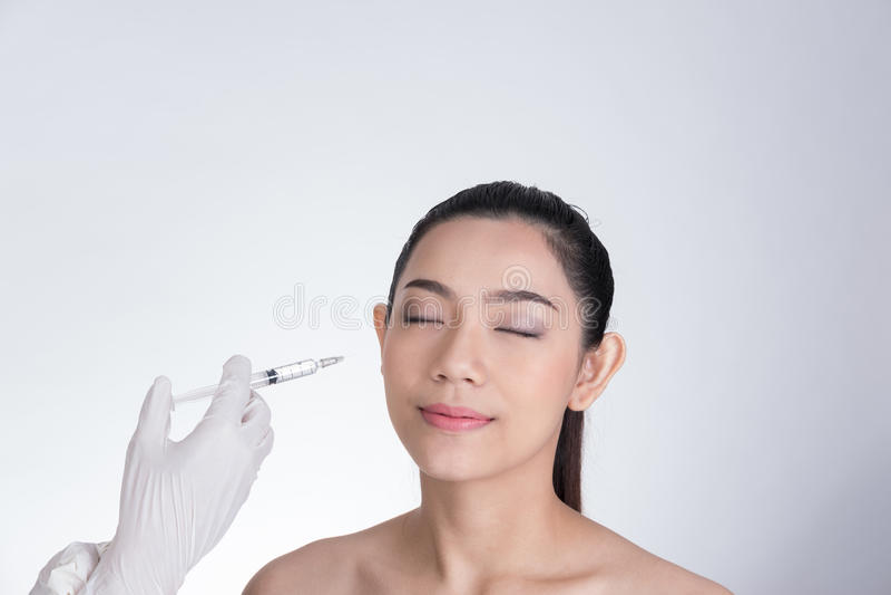 Cuide la mano del ` s que hace la inyección del botox en cara del ` s de la muchacha Asia joven fotos de archivo