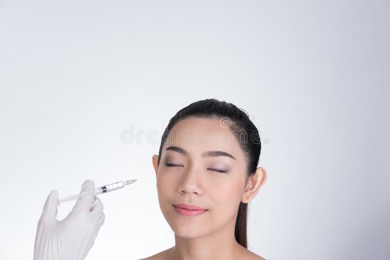 Cuide la mano del ` s que hace la inyección del botox en cara del ` s de la muchacha Asia joven foto de archivo libre de regalías