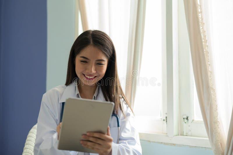 Cuide a la mujer asiática sonriente que trabaja en una tableta digital foto de archivo libre de regalías