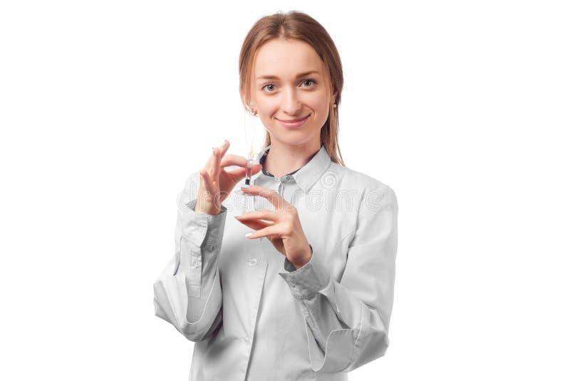 Cuide a la mujer en la capa blanca del laboratorio con la jeringuilla fotos de archivo libres de regalías