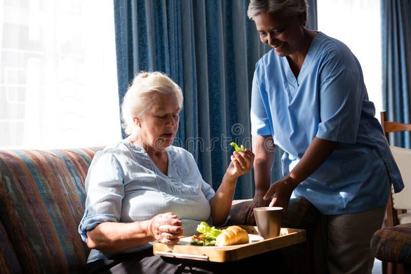 Cuide a la mujer mayor que hace una pausa que come la comida en la tabla imagen de archivo