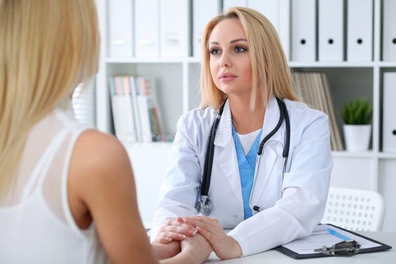 Cuide a la mujer que tranquiliza a su paciente femenino mientras que lleva a cabo las manos Concepto de la medicina, de la ayuda  imagen de archivo libre de regalías