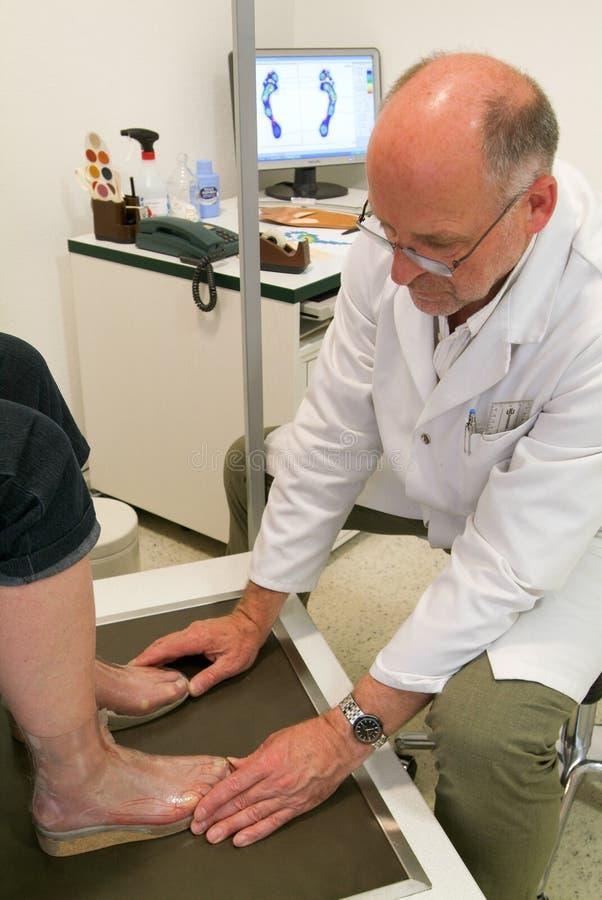 Cuide la preparación de las plantillas ortopédicas para un paciente en su estudio imagen de archivo libre de regalías