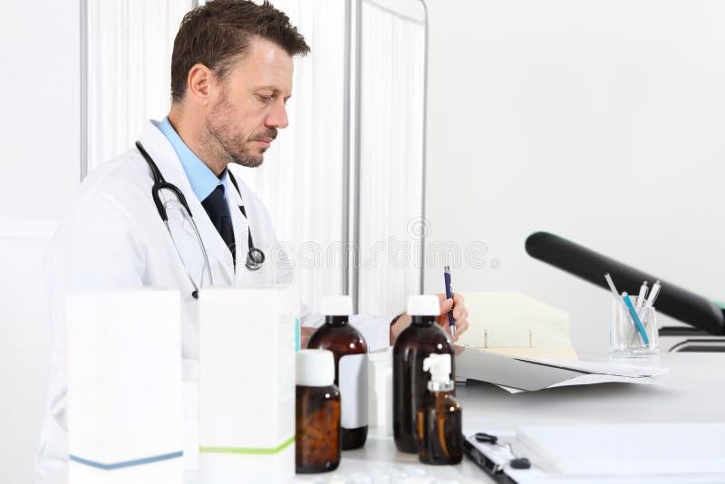 Cuide la prescripción de la escritura en el escritorio en oficina médica con las drogas foto de archivo libre de regalías