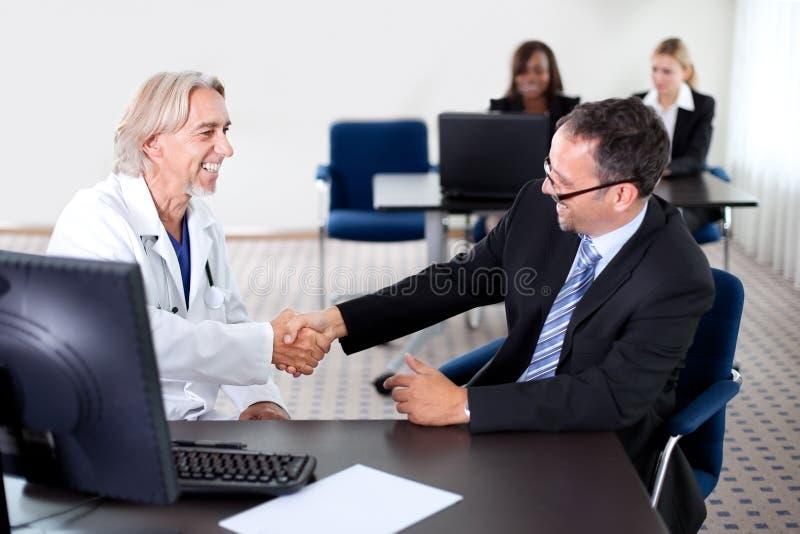 Cuide la sacudida de las manos con un paciente en un escritorio imágenes de archivo libres de regalías