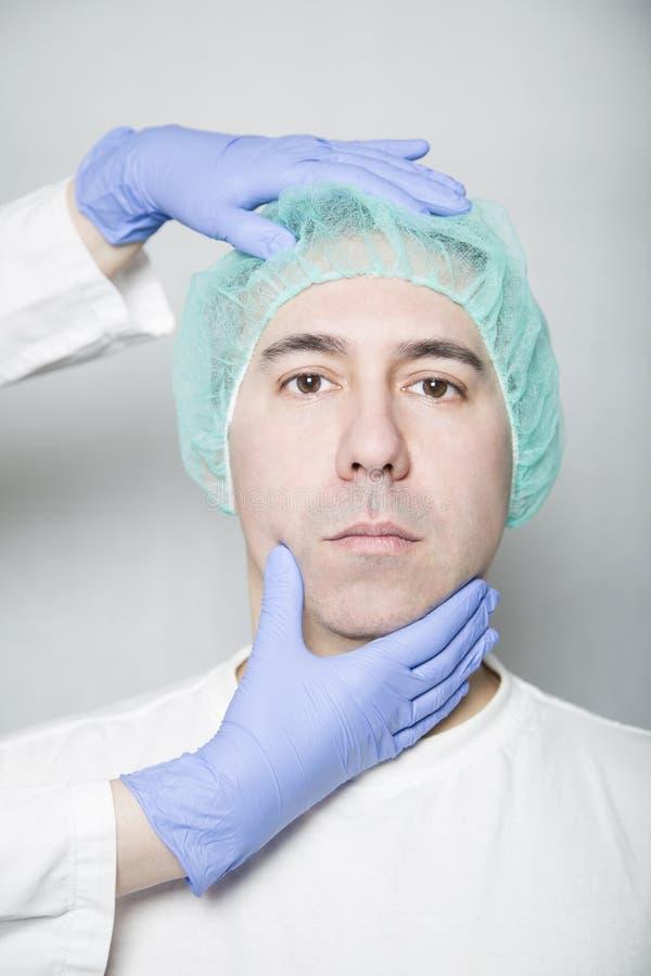 Cuide las manos que llevan a cabo la cabeza del paciente en un casquillo médico foto de archivo libre de regalías