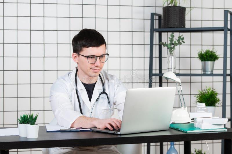 Cuide las notas pacientes que entran sobre un ordenador portátil en cirugía imagenes de archivo