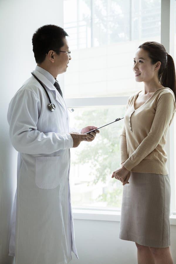 Cuide llevar a cabo cartas médicas y la discusión con un paciente femenino en el hospital imagen de archivo libre de regalías
