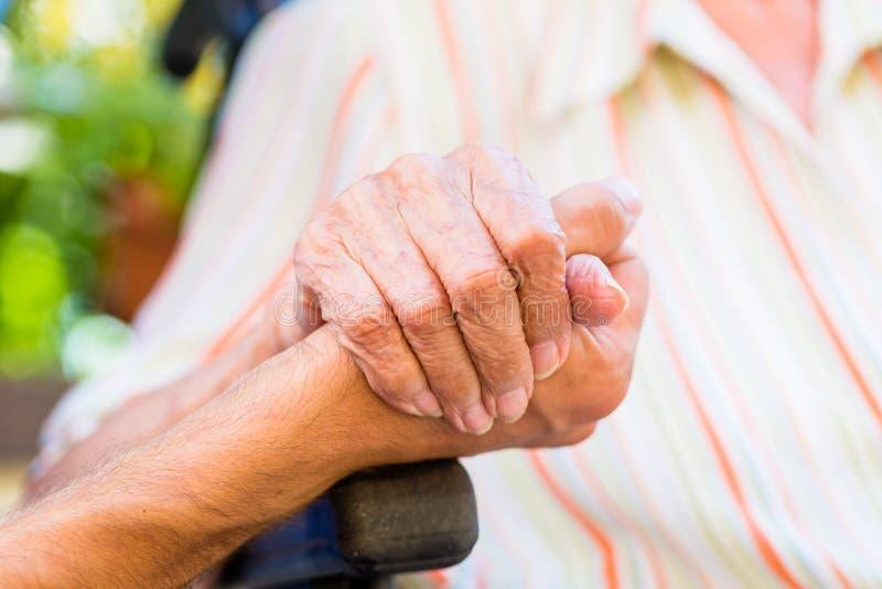 Cuide llevar a cabo la mano de la mujer mayor en silla de rueda fotografía de archivo