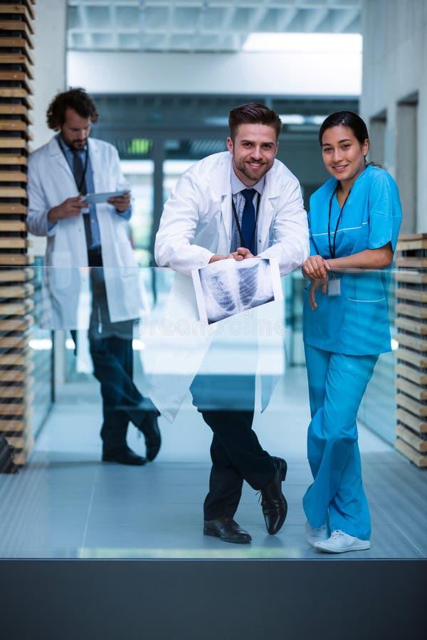 Cuide llevar a cabo la radiografía que se coloca con la enfermera en hospital imágenes de archivo libres de regalías