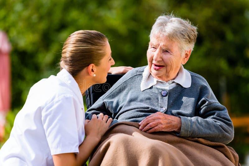 Cuide llevar a cabo las manos con la mujer mayor en silla de ruedas foto de archivo libre de regalías