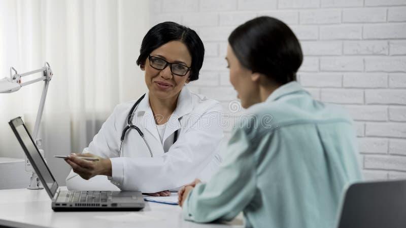 Cuide mostrar los resultados de la prueba en el ordenador portátil, tratamiento eficaz, recuperación paciente imagenes de archivo
