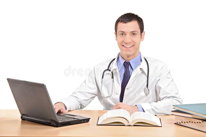 Cuide sentarse en un escritorio y el trabajo en el ordenador portátil fotos de archivo