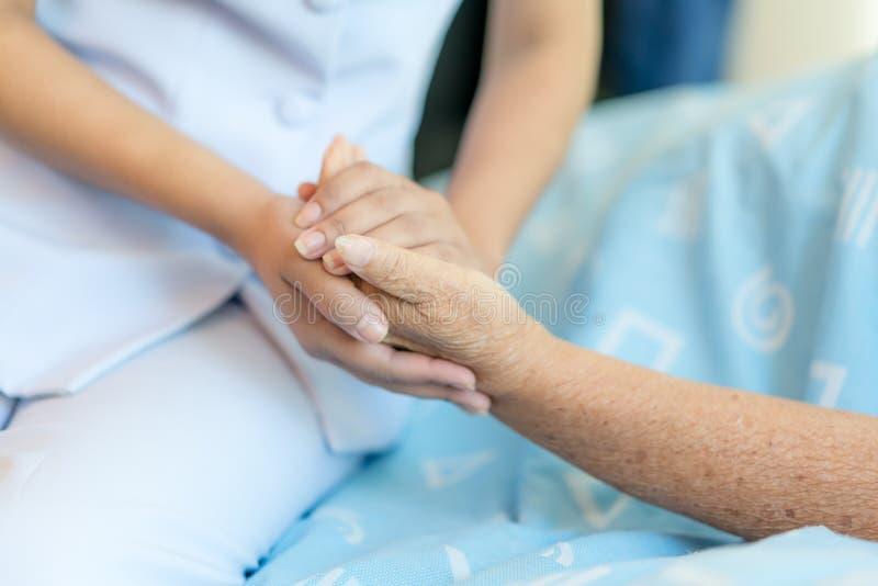 Cuide sentarse en una cama de hospital al lado de una más vieja mujer que ayuda a h imagenes de archivo