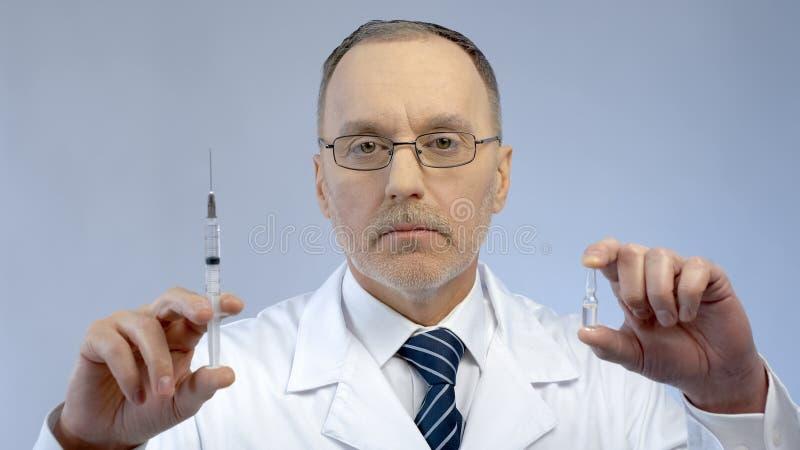 Cuide sostener la jeringuilla y la ampolla, prescribiendo la medicación eficaz al paciente imagen de archivo libre de regalías