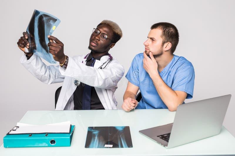 Cuide tener conversación con su colega y llevar a cabo la radiografía en oficina médica Oficina médica fotos de archivo libres de regalías