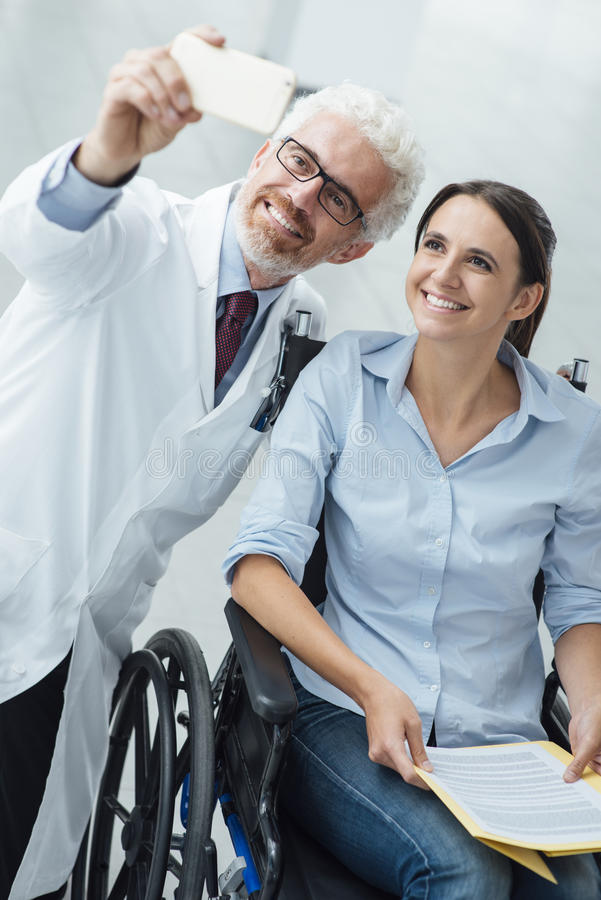 Cuide tomar un selfie con una mujer en silla de ruedas fotos de archivo libres de regalías