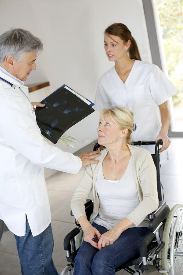 Cuide y cuide tomar el coche del paciente en silla de ruedas fotografía de archivo libre de regalías