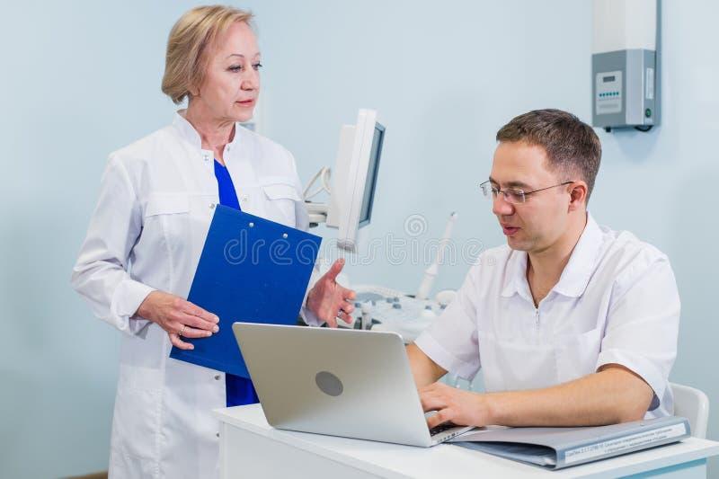 Cuide y cuide el repaso de la información paciente sobre un ordenador portátil en un ajuste de la oficina fotografía de archivo