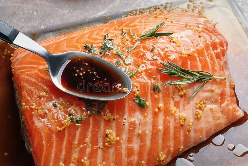 Cuillère avec la marinade sur le filet saumoné cru photos libres de droits