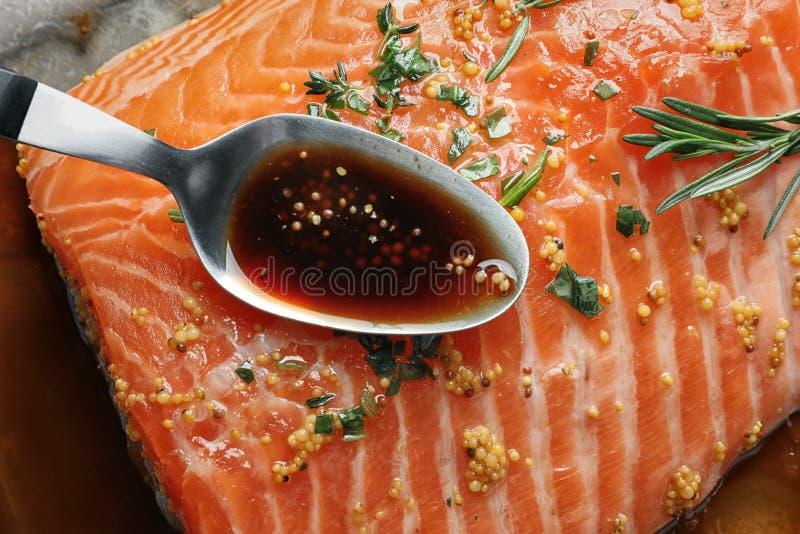 Cuillère avec la marinade sur le filet saumoné cru photo stock