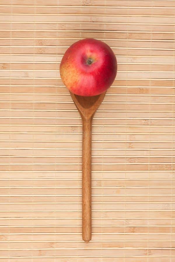 Cuillère avec la pomme rouge se trouvant sur le tapis en bambou photos libres de droits