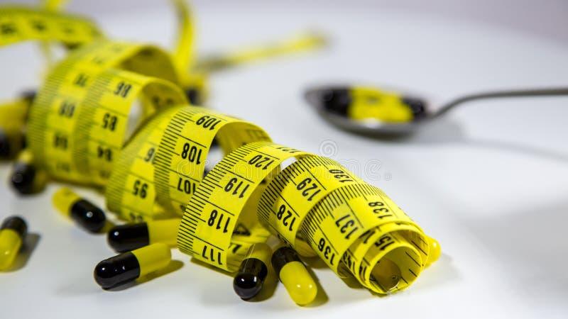 Cuillère avec les pilules et la bande de mesure pour représenter l'industrie de pilule de régime images libres de droits