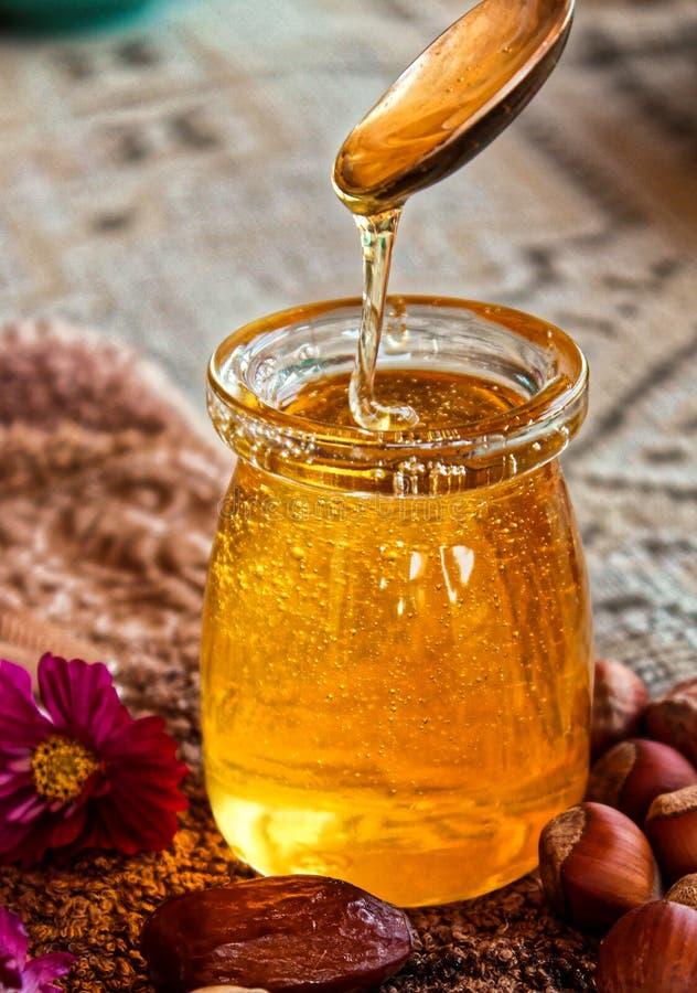 Cuillère d'argent dans le pot en verre de miel photographie stock