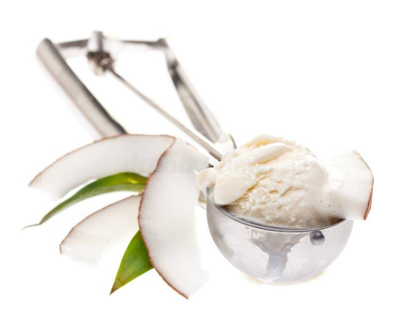 Cuillère de crème glacée avec la crème glacée de noix de coco tranches de noix de coco et de feuilles d'isolement sur le fond bla image stock