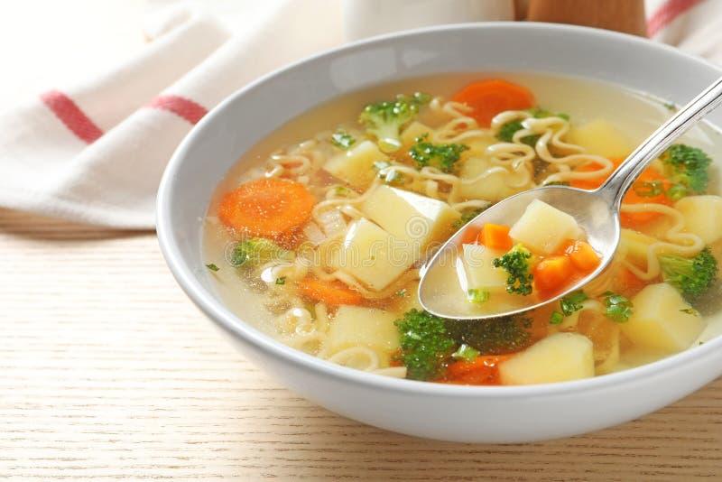 Cuillère de potage aux légumes fait maison frais au-dessus de pleine cuvette sur la table en bois images libres de droits
