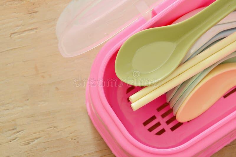 Cuillère de soupe et baguettes en plastique colorées dans la boîte rose photos stock
