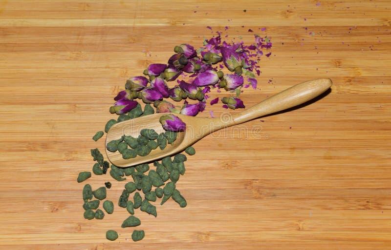 Cuillère en bambou avec le thé de ginseng et le bouton de rose sec images libres de droits