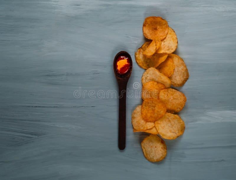Cuillère en bois avec le ketchup et puces sur un fond en bois bleu, vue supérieure, l'espace pour le texte images libres de droits