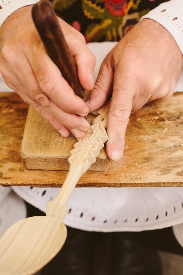 cuillère en bois découpant sculptant les artisans roumains image libre de droits