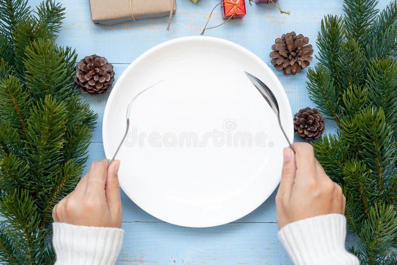 cuillère et fourchette au-dessus de plat vide avec la décoration de Noël, préparation de bonne année et Noël de participation de  images libres de droits