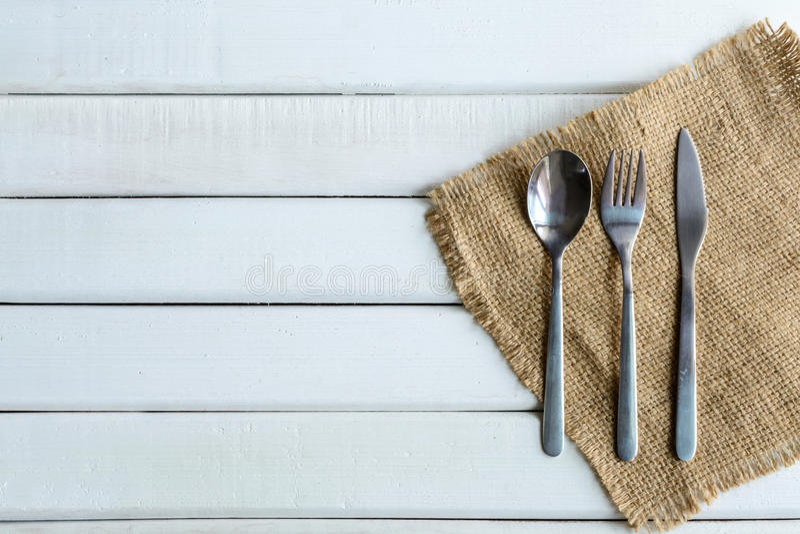 Cuillère et fourchette en bois avec le plat sur le bois blanc photographie stock libre de droits