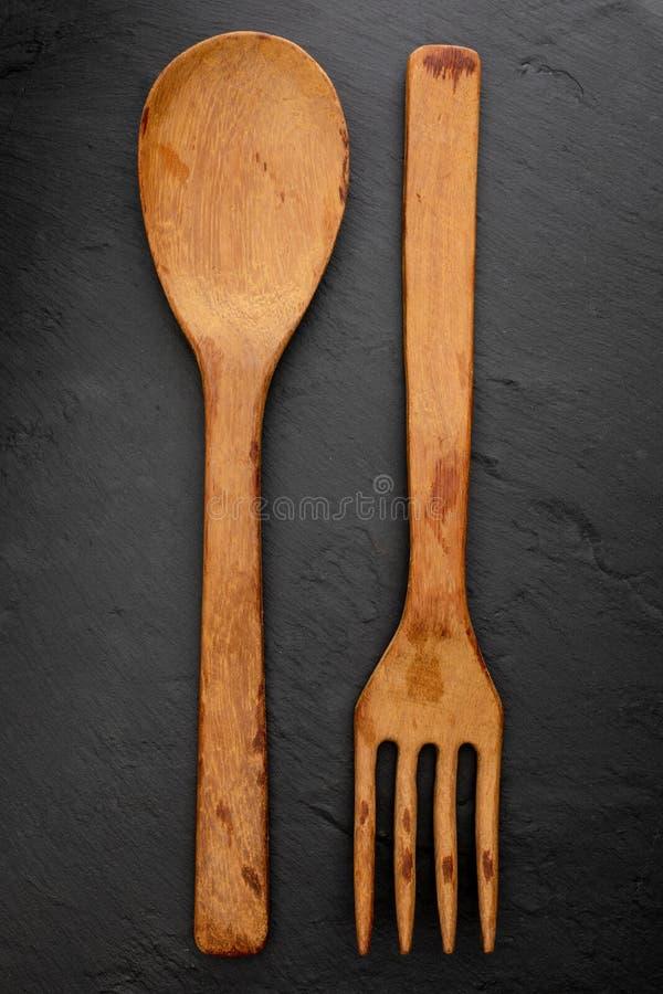 Cuillère et fourchette en bois sur le fond noir texturisé de tableau L'espace pour insérer votre texte ici photos libres de droits