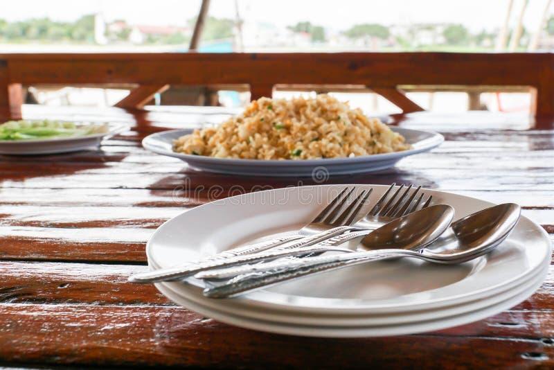 Cuillère et fourchette inoxydables des plats blancs sur la table en bois avec le contexte de riz frit photos libres de droits