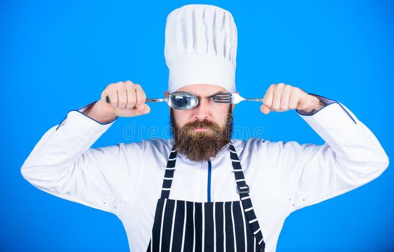 Cuillère et fourchette strictes sérieuses de prise de visage de chef Concept de procédé de cuisson Laisse le plat d'essai Chef af photos stock