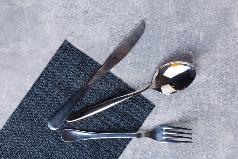 Cuillère, fourchette et couteau sur une serviette de portion de cuisine image libre de droits