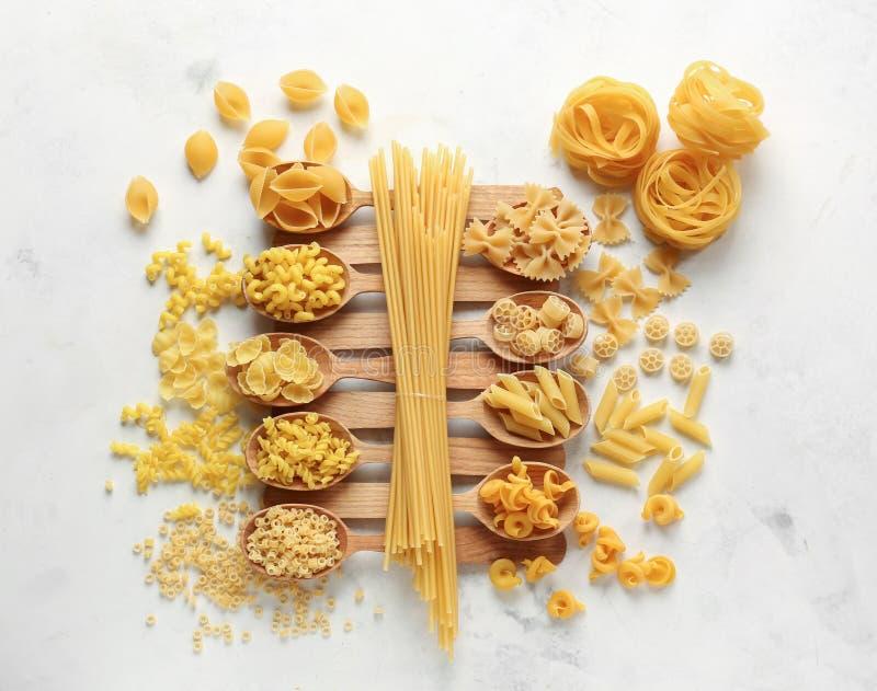 Cuillères avec différents types de pâtes crues sur la table blanche images libres de droits