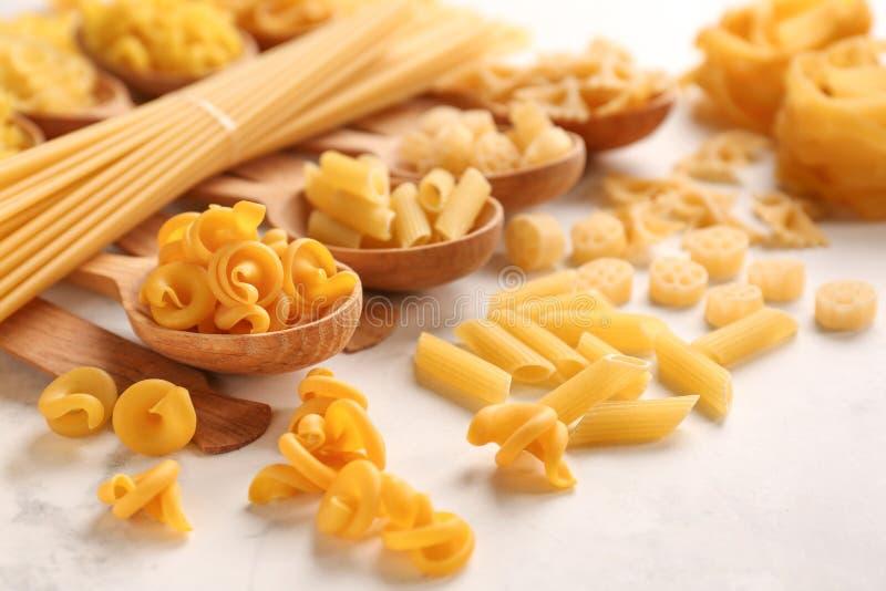 Cuillères avec différents types de pâtes crues sur la table blanche images stock